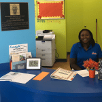 A CHILD Center staff member smiles from the reception area of the building.