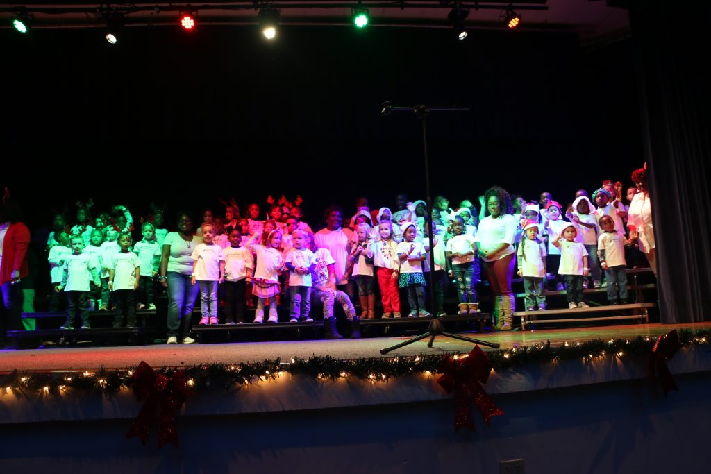 A large group of young children on a stage below colorful lights during a Head Start holiday performance