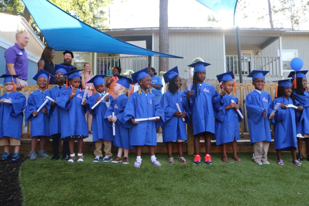 The first graduating class of the CHILD Center stands in a line, wearing blue graduation regalia and holding paper scrolls.