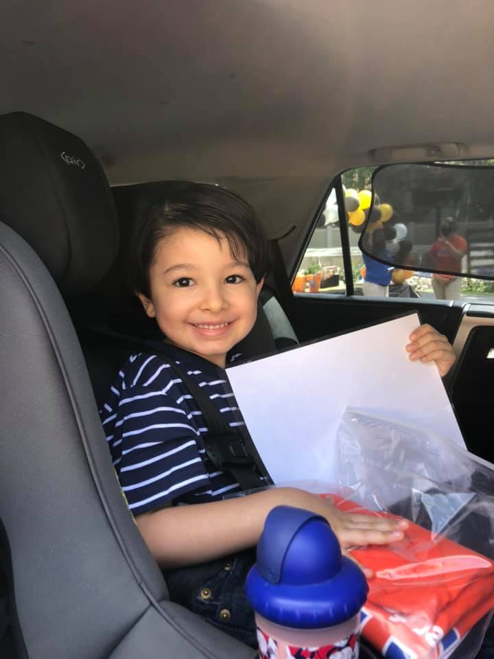 """A 2020 grad sits in a car and holds a """"Bachelor of Preschool"""" diploma"""