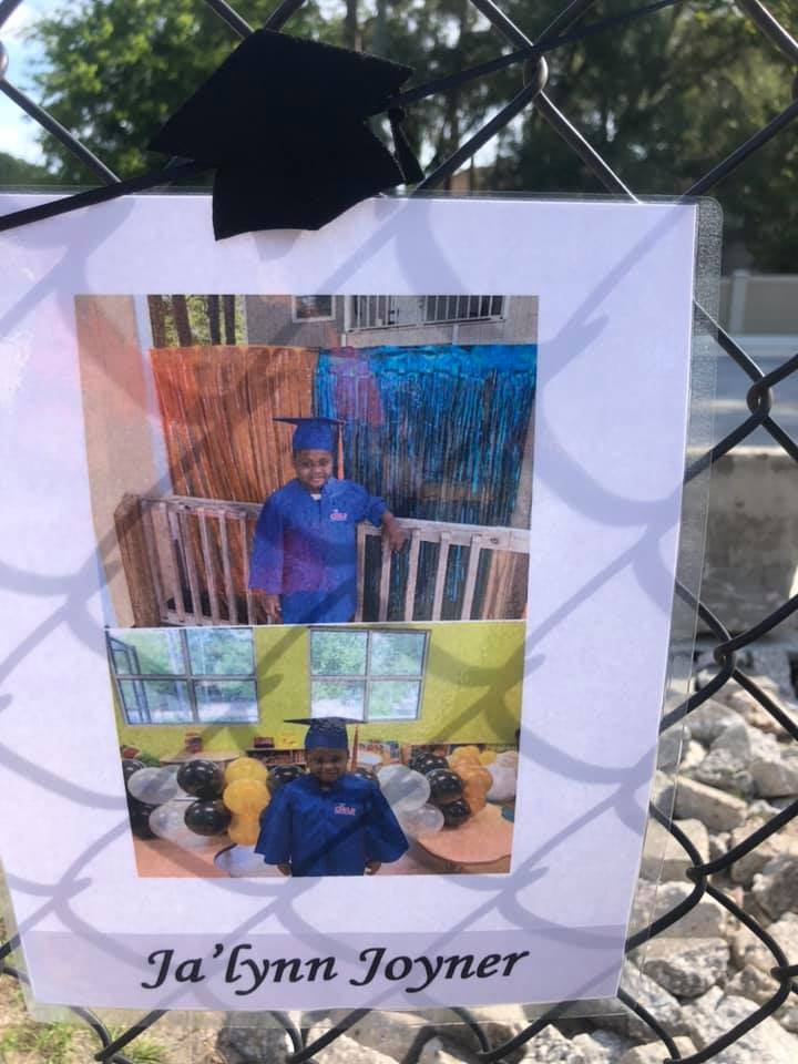 A photo of a 2020 CHILD Center graduate in blue regalia displayed on the CHILD Center fence