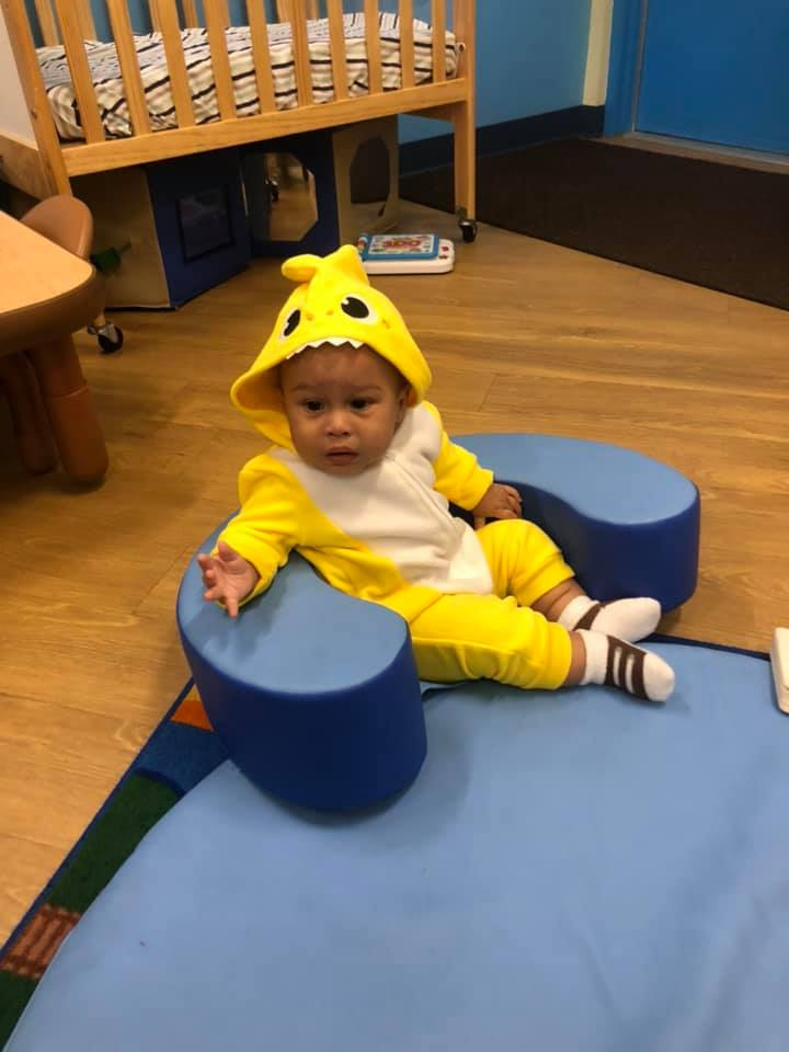 A CHILD Center student wearing a yellow onesie with a hood