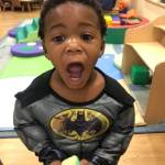 A CHILD Center student wearing a Batman costume and making a face for the camera