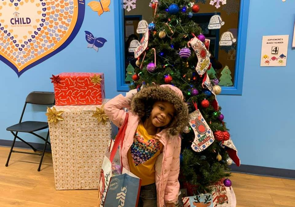 A CHILD Center student holds a large bag and stands in front of a decorated Christmas tree.