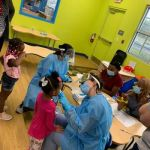Two representatives from the UF Dental program give dental screenings to children at the CHILD Center for Early Learning.