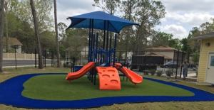 A shaded playground structure behind the CHILD Center with orange slides and platforms for climbing
