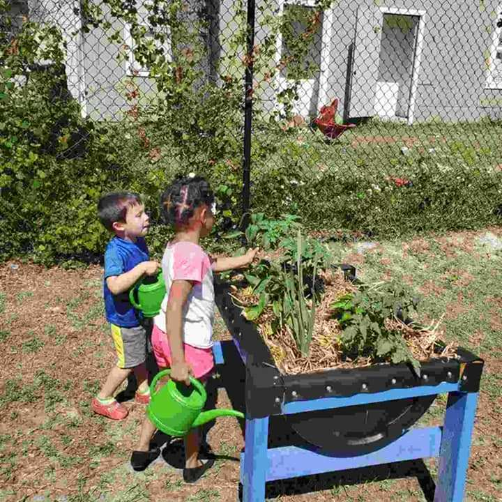 Two CHILD Center students observe together the plants growing at the CHILD Center in April 2021.