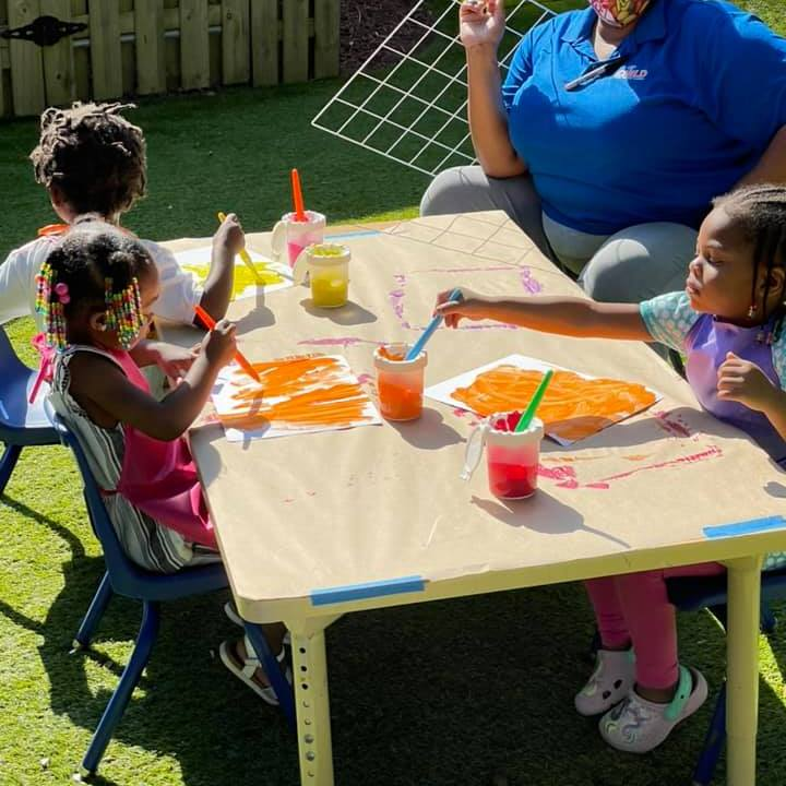 Three young children sit at an outdoor table creating yellow and orange paintings with their CHILD Center teacher