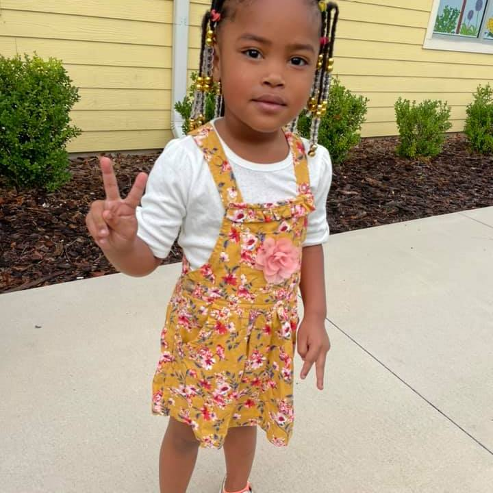 A young child makes a peace sign in front of the CHILD Center