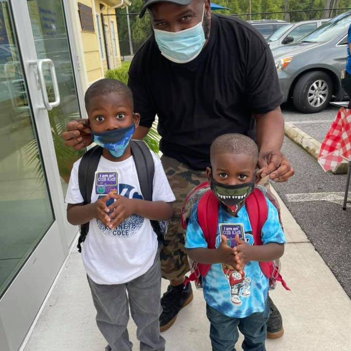 A grown-up walks two young children into the CHILD Center on the first day of the 2021-22 school year