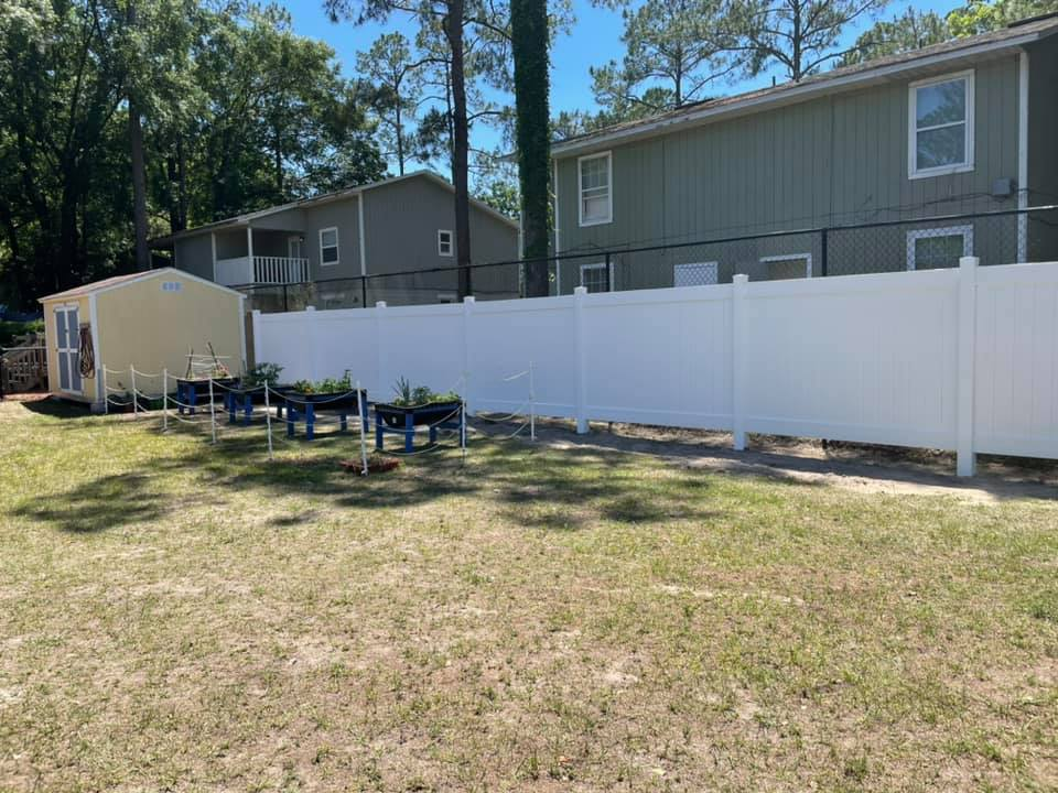 A new, finished white fence behind the CHILD Center outdoor area