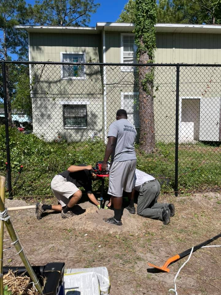 Three volunteers prepare the space where a new fence will be erected behind the CHILD Center