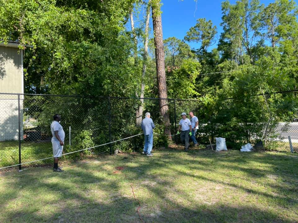Gainesville Rotary Club volunteers measure out the space for a new fence behind the CHILD Center in Summer 2021