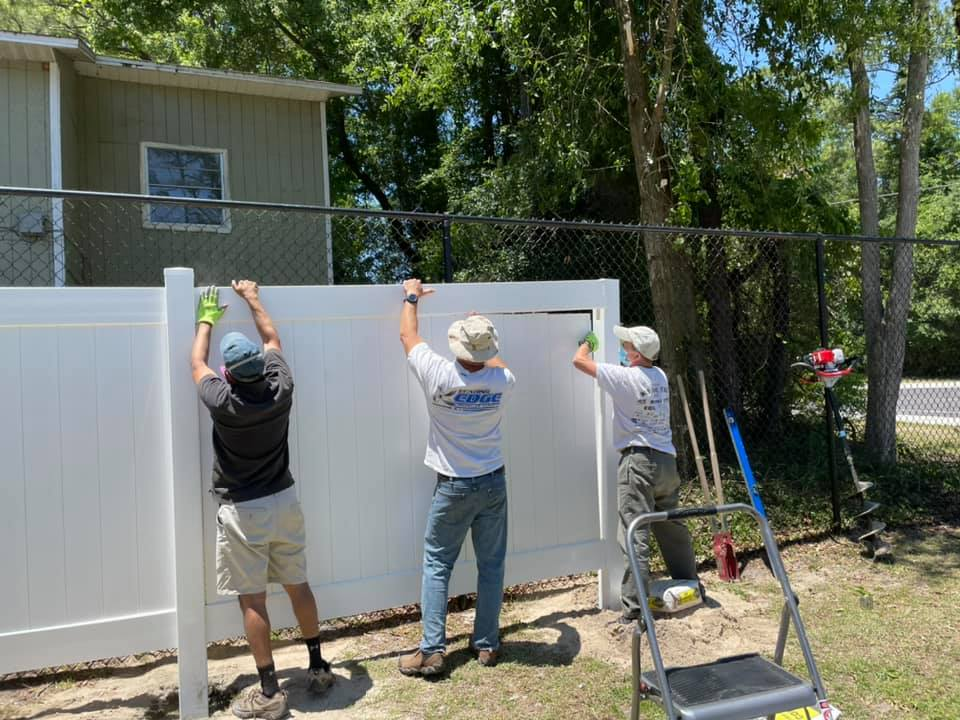 Gainesville Rotary Club members work together to install a new white fence behind the CHILD Center in Summer 2021