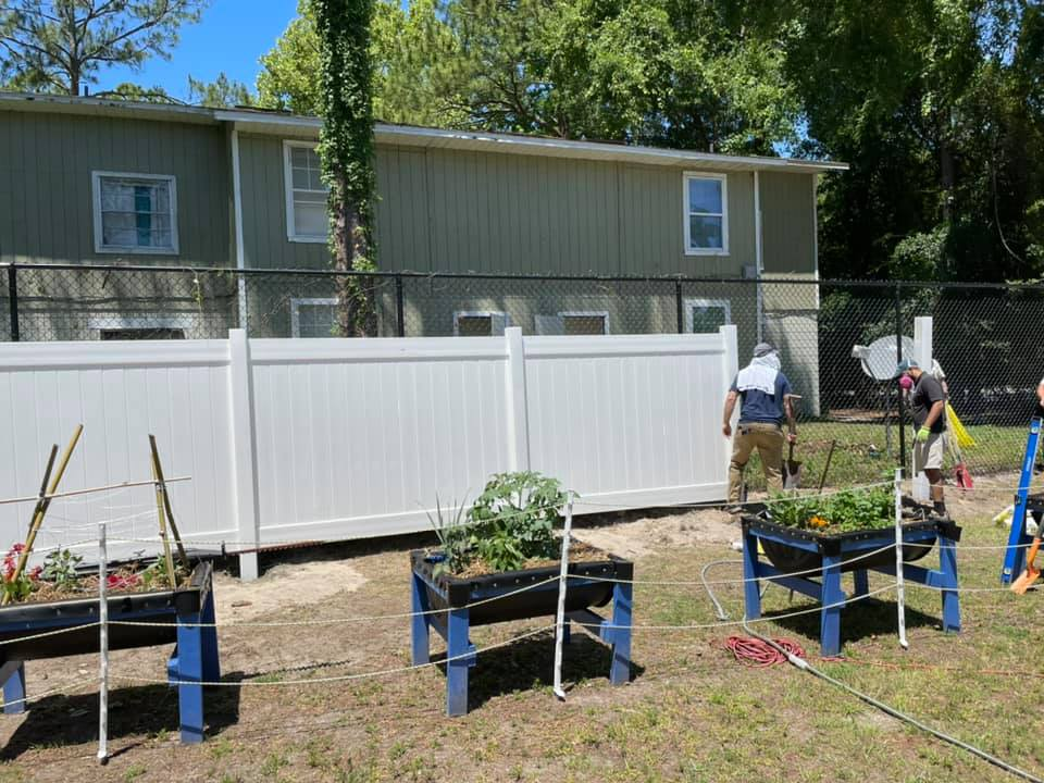The raised garden beds at the CHILD Center stand in front of a new finished fence