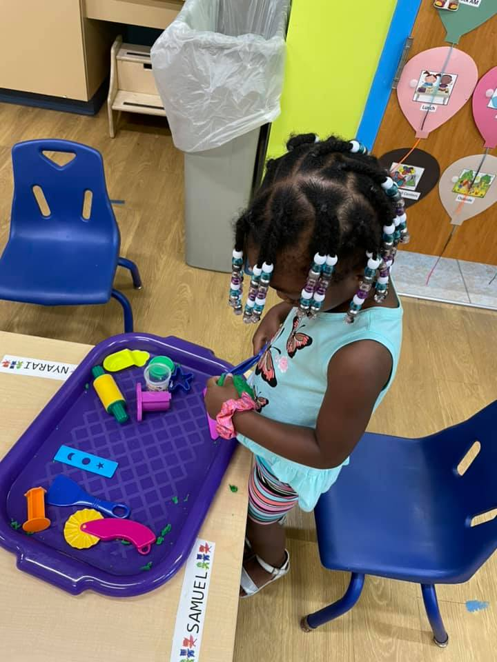 A young girl plays with toys on a purple tray at the CHILD Center