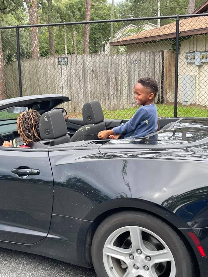 """A child grins widely while riding in the back of a convertible during the """"Buzz-By"""" graduation celebration"""