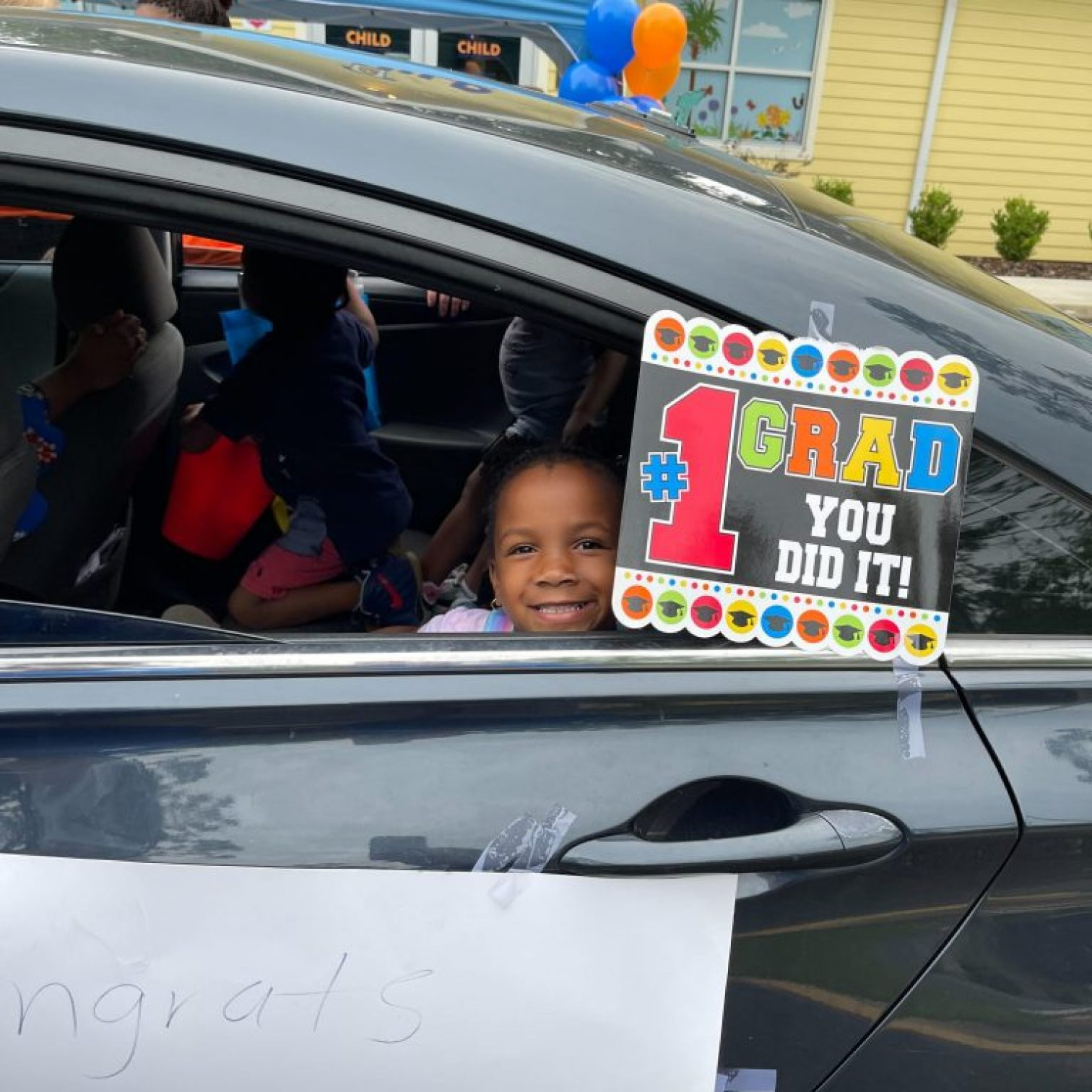 """A child smiles out the window of a car decorated with a sign that reads, """"#1 GRAD, YOU DID IT!"""""""