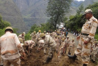 Indian para military soldiers clears the road hit by landslide near Rudraprayag, in northern Indian state of Uttrakhand, Thursday, June 20, 2013.