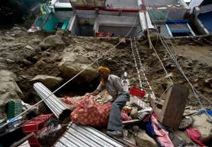 A landslide-damaged building stands on the edge of a newly-created precipice as an Indian shopkeeper salvages a sack of onions from the premises in Govind Ghat
