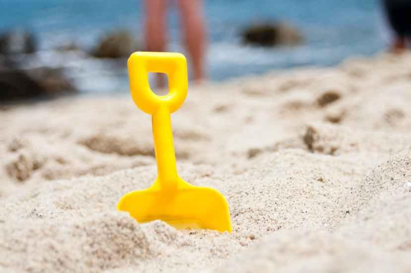 yellow shovel half buried on sand near the ocean