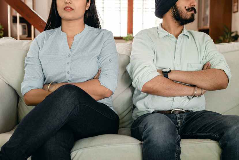 anonymous ethnic couple sitting on sofa having marriage issues