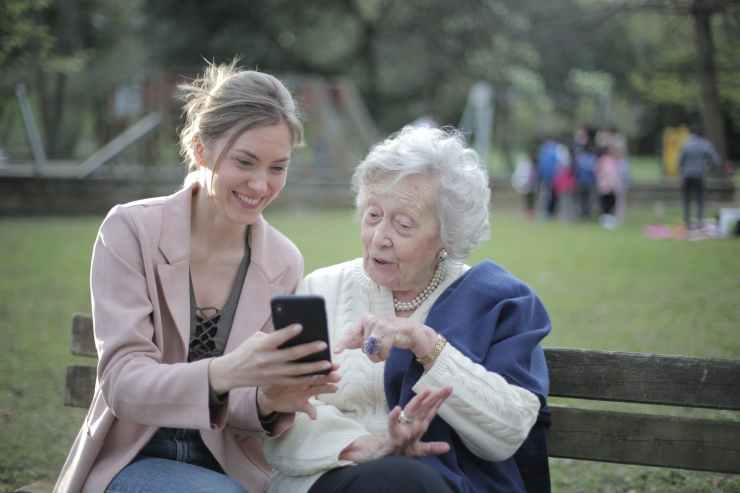 cheerful senior mother and adult daughter using smartphone together