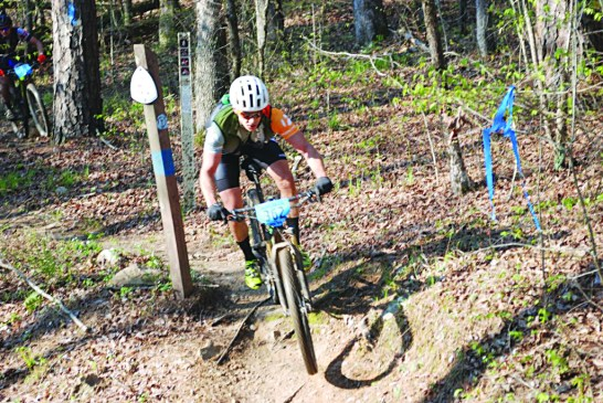 Some terrain along the Ouachita Challenge course is particularly challenging, or particularly exciting, according to riders. Shown here is an unidentified rider airborne as he comes off a sharp drop-off near Big Brushy Recreation Area.  The next challenge facing riders, at this point, is Blowout Mountain. Riding 60 miles over scenic, but rough, terrain has made the Ouachita Challenge a much sought after race. Photo by Derwood Brett