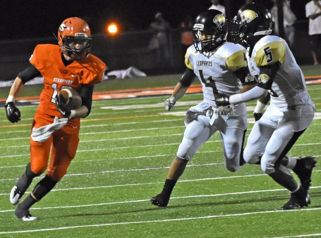 Zach Jamison (13) makes his way around the Leopard defenders during the Scrappers' 47-8 win over De Queen Friday night at Scrapper Stadium.