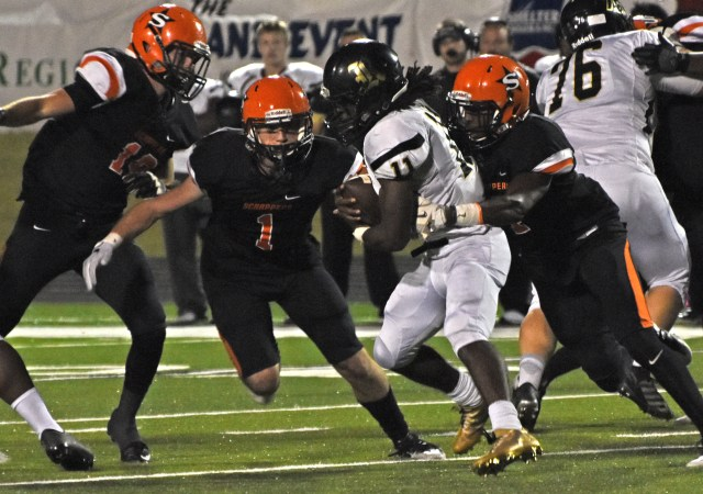 Hunter White (1) and Ty Pettway (4) move in for the tackle on Robinson Senator Myles Fells (11) Friday night at Scrapper Stadium.