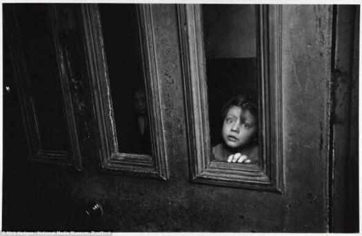 Призраки: девочка выглядывает из панели окна в двери в коммунальной квартире в доме в Токстет, Ливерпуль март 1969.