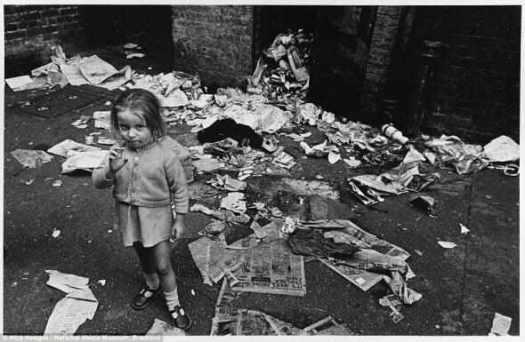 Просто еще один день: девочка в грязной одежде позирует для фото в лондонском Ист-Энде в 1969 году среди груды мусора и расквашенных газет, которые окружают подвальное помещение, в котором она жила.