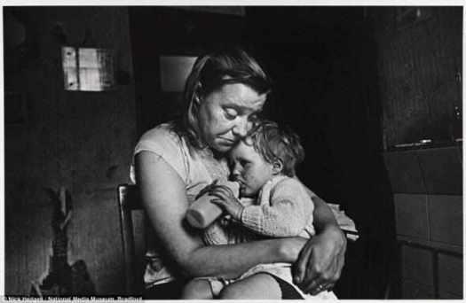 Лишенные: г-жа Т и ее семья из пяти человек, включая ее ребенка, изображенного на этой фотографии в мае 1969, жили в развалювающимся общежитии, принадлежащему сталелитейному комбинату в Шеффилде. У них не было ни газа, ни электричества, ни горячей воды, ни ванной комнатой. Миссис T была вынуждена готовить на огне в гостиной.