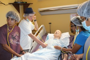 Students care for a mock patient during a nursing demonstration at WNMU during the 2014 Health Careers Academy