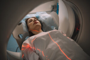 woman lying on ct scanner bed during tomography test