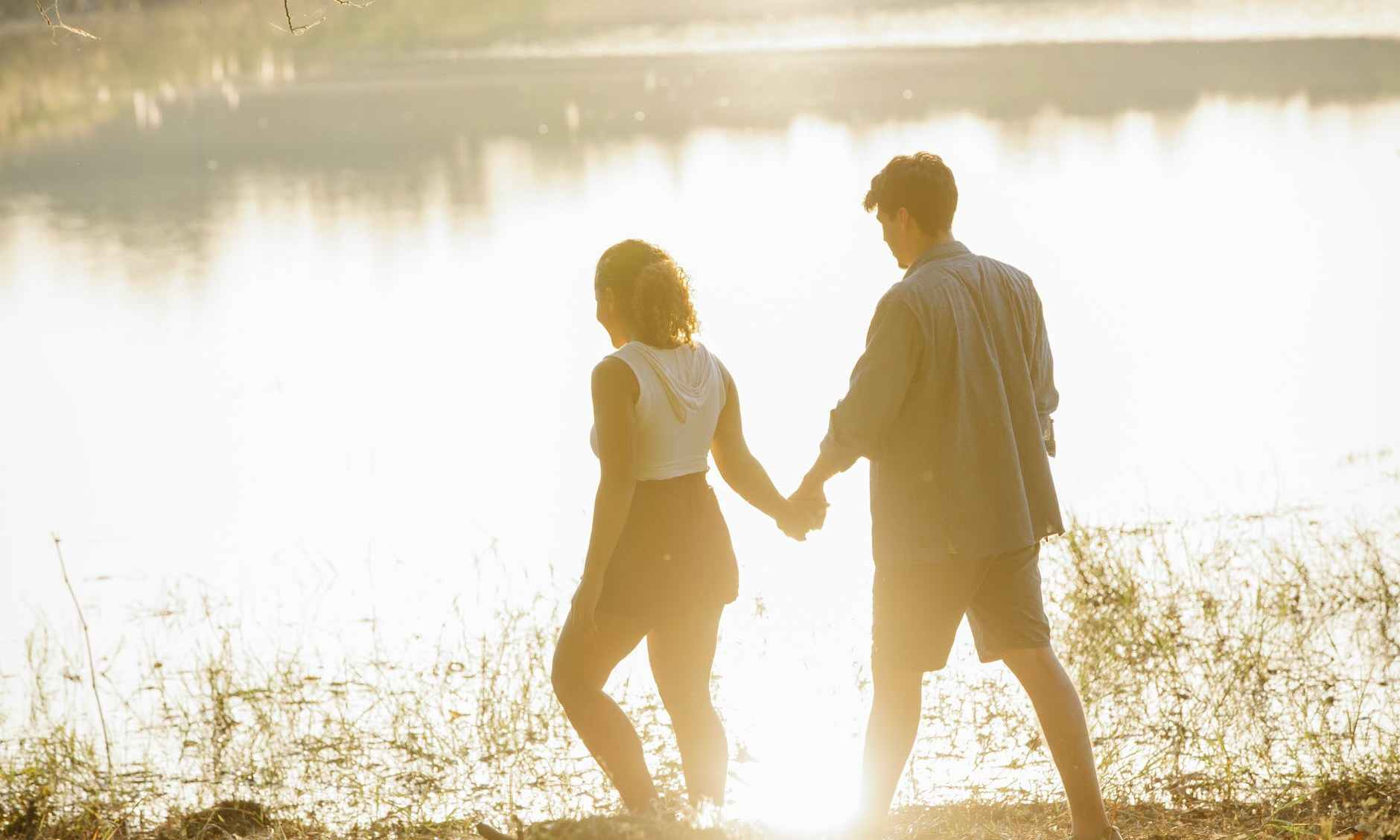 unrecognizable couple holding hands during stroll on lake coast