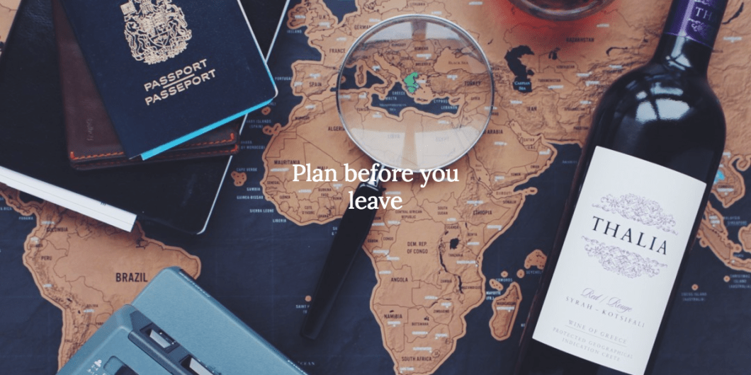 Map, pass, and wine with a sign 'Plan before you leave' to prepare for traveling