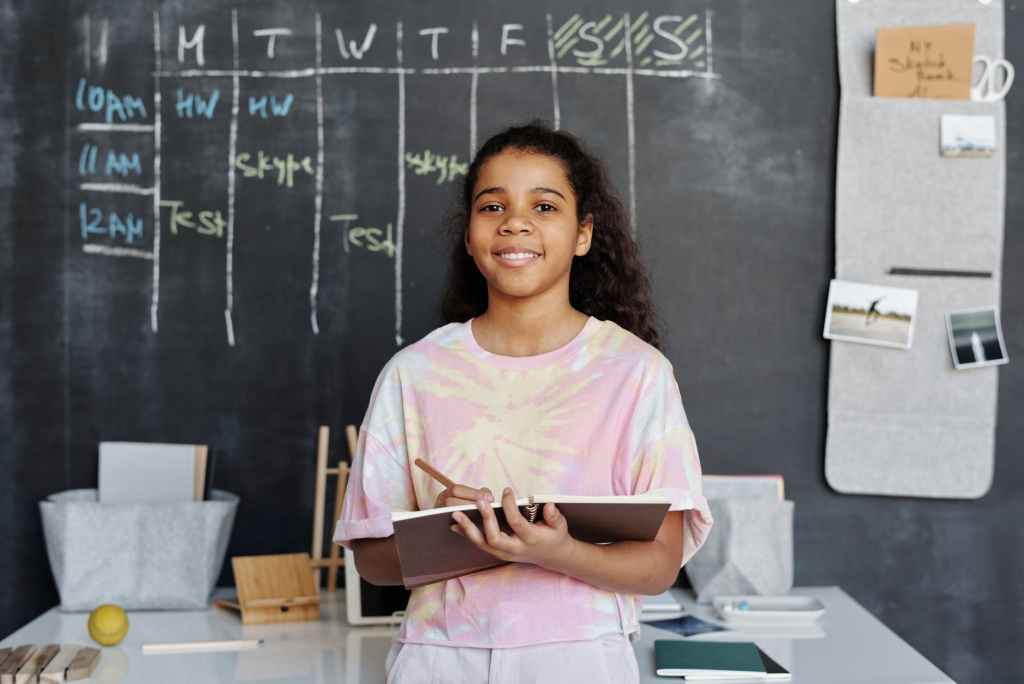 girl in pink shirt holding notebook