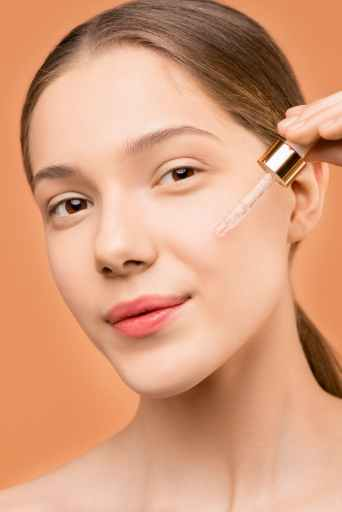Girl applying diy hyaluronic acid serum to her face.