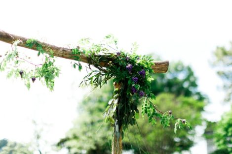 A delicate vine of blooming wisteria on a rustic, cedar arbor for a waterside wedding - Photo credit: Adams Photography