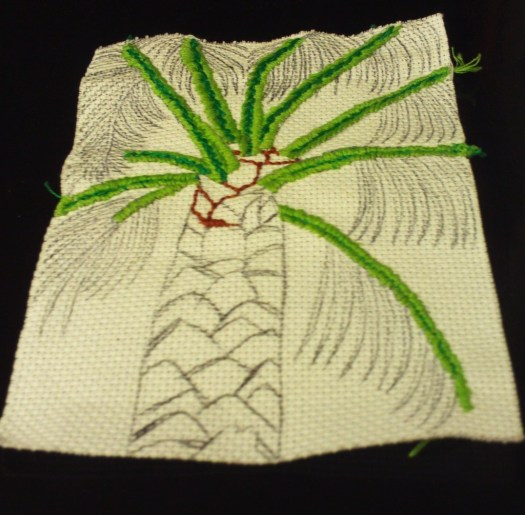 Here I am starting to cross stitch in the darker portions of the palm tree trunk with an outline stitch.