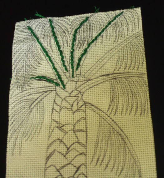 Continuing to cross stitch on the darker portions of the palm tree branches.