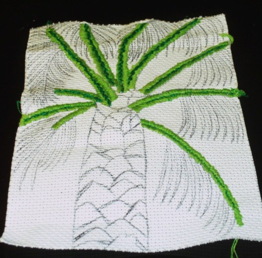 Here I have finished cross stitching on the branches of the palm tree.