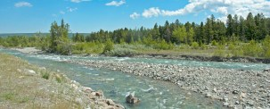 cropped-Rushing-Stream-Clouds-Blue-Sky-River-Rocks-Many-Glacier-Area1.jpg