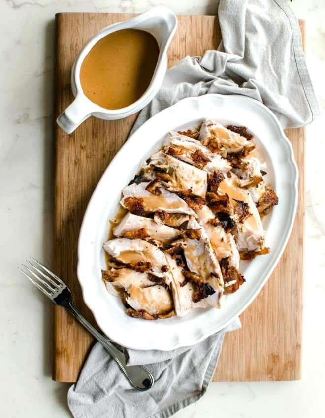 A white platter filled with turkey breast that is topped with crispy skin and gravy with a dish of gravy on the side.