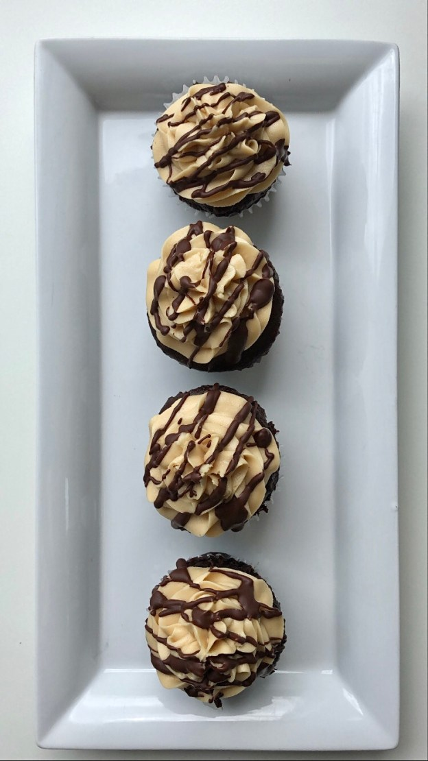 Top-view of 4 buttercream cupcakes with drizzled chocolate placed a white plate.