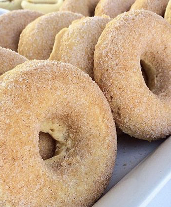 A close-up side-view of vanilla donuts coated with cinnamon sugar.
