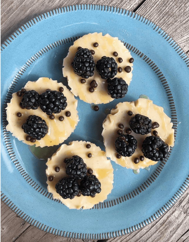 Four Cheesecakes topped with blueberry on a blue plate