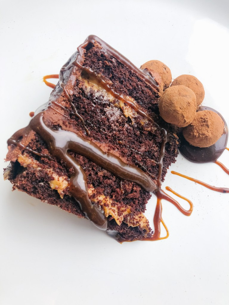 Top view of chocolate cake slice, four layers chocolate frosting, caramel sauce, topped with chocolate truffle