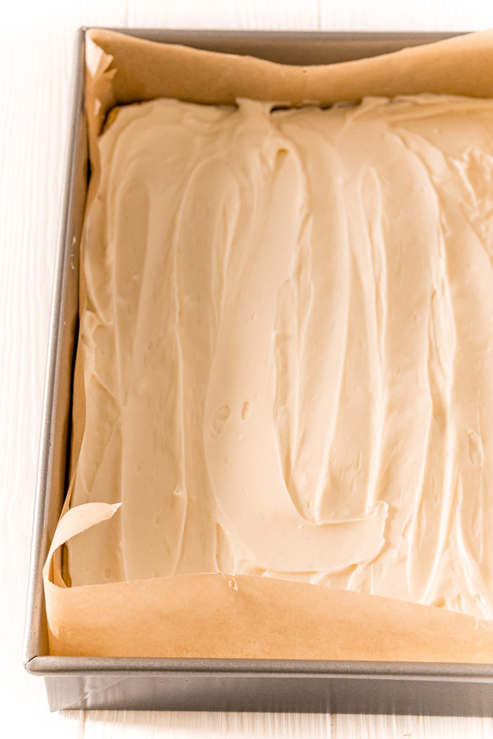 picture of dough and cream cheese in a baking dish with parchment paper